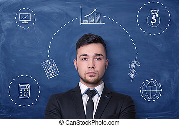 Businessman on blue blackboard background with chalk drawing of small charts, graphs, money sack and calculator.