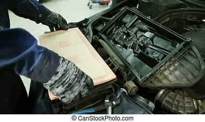 In service station mechanic installs a new air filter inside the box.