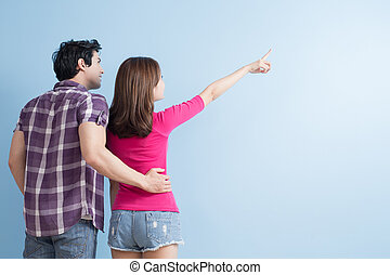 young couple show something