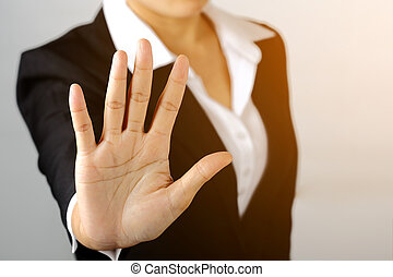 Serious business woman shows stop sign talk to hand gesture...