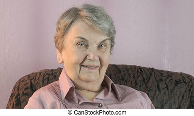 Old woman laughs on the camera indoors - Old woman sitting...