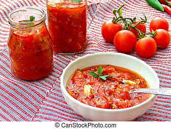 Tomato sauce - Cup and jars with spicy tomato sauce for...