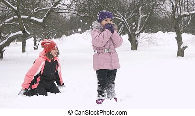 Slow motion of joyful kids playing in snow. Two happy girls having fun outside winter day