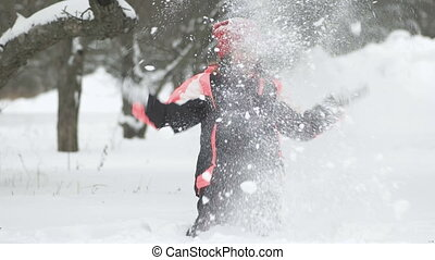 Slow motion of joyful child playing in snow. Happy girl having fun outside winter day