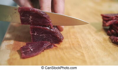 On a wooden board with a knife thinly sliced pieces of raw meat.
