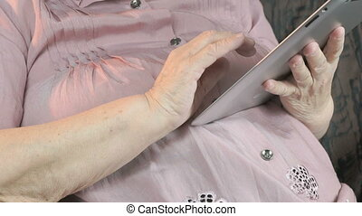 Aged woman 90s holding the silver tablet computer - The aged...