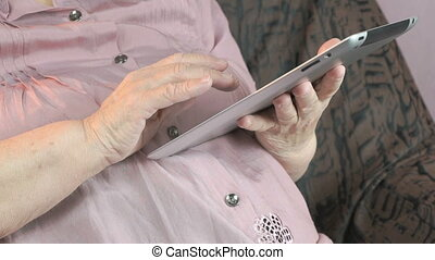 Elderly woman holding the silver tablet computer - Elderly...