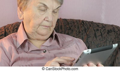 The aged woman holding the silver tablet computer - The aged...