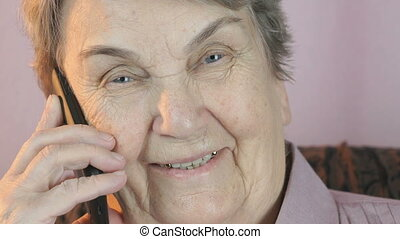 Aged woman 80s smiling talks on the mobile phone. Close up