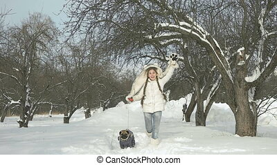 Slowmotion Happy girl playing with her dog on snow and having fun outside winter day