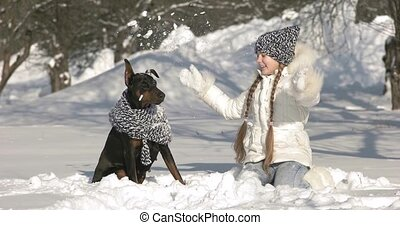 Happy girl playing with her dog on snow and having fun outside winter day