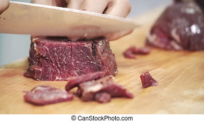 On board a human being cut into chunks with a knife red meat...