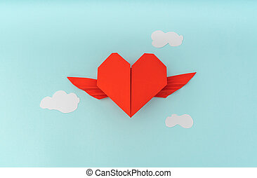 Red paper origami heart with wings and cloud on blue...