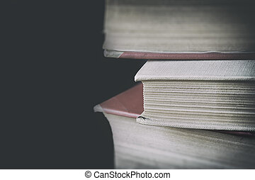 A pile of aged books - Three books in old shells placed in a...