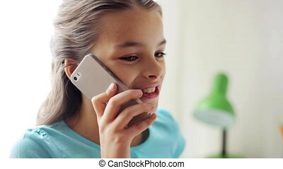 smiling girl calling on smartphone at home - people,...