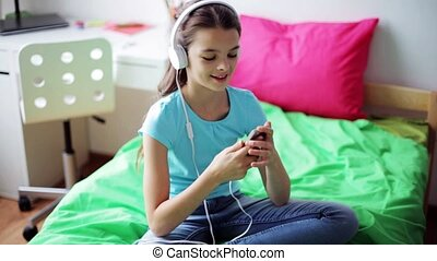 happy girl with smartphone and headphones at home - people,...
