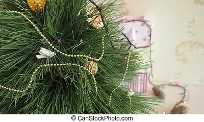 Man decorates a Christmas tree. Hanging Ornaments on a...
