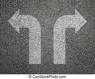 Two white arrows on asphalt