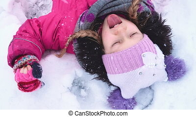 child girl catching a snowflakes with her tongue close up...