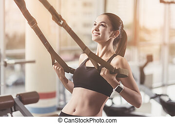 Delighted woman training hard in a gym