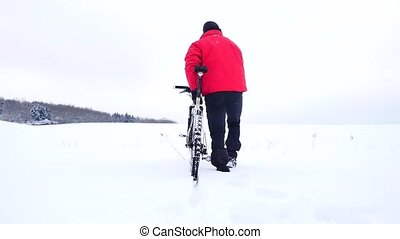 Man with mountain bike on snowy filed. Biker is pushing bike...