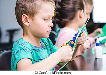 Schoolchildren making applique with colorful paper and...