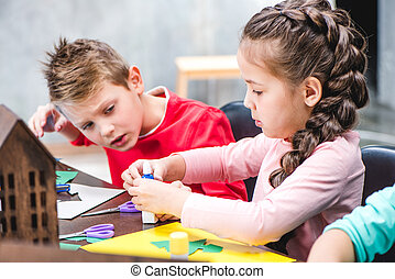 Schoolchildren making applique with colorful paper, glue and...