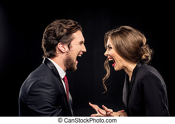 Laughing couple in formal wear looking at each other on...