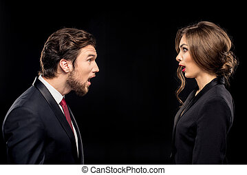 Shocked couple in formal wear looking at each other on black