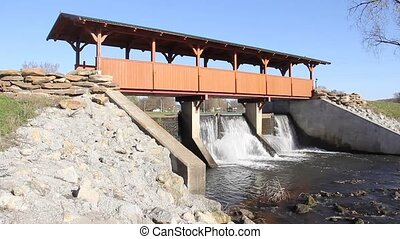 Earth dam under a wooden bridge - Water flowing through an...