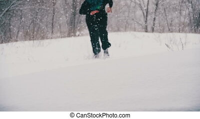 Man Jumps and Dives Headlong into the Snow and Have Fun in the Winter Pine Forest. Slow Motion
