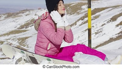 Young woman with snowboard in mountains - Smiling young...