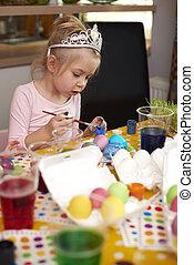 Cute girl focused on her handmade easter eggs