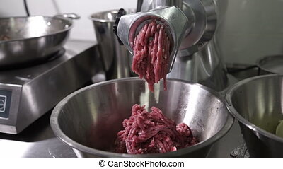 Electric meat grinder of metal scrolls red meat in the...