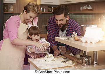 Little girl making her first cookie with parents