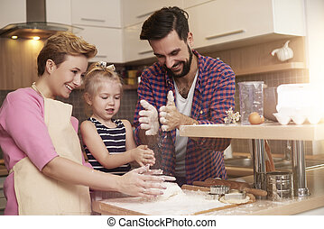 Little girl spending time with parents in the kitchen