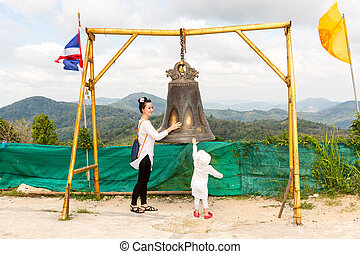 Child and mom near Thai gong in Phuket. Tradition asian bell...