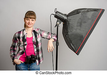 Portrait of a girl the photographer at the studio softbox