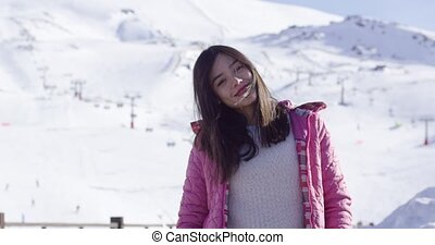 Carefree young woman in snowy ski resort - Upper body...