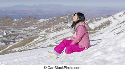 Beautiful asian girl sitting at the snow in hight mountains....
