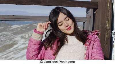 Beautiful asian girl enjoys sunny winter weather on the...