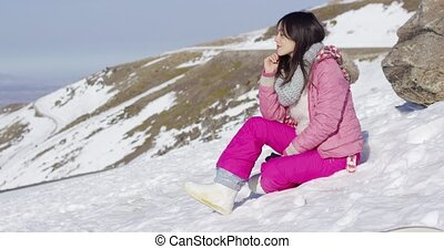 Smiling woman sat on snowy mountain summit - Side view of...