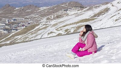 Young woman on snowy mountain summit - Side view of young...