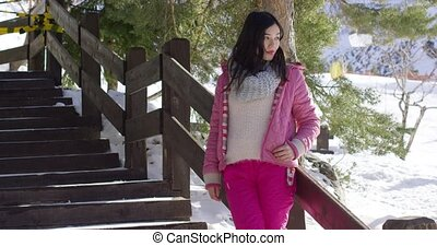 Woman in pink snowsuit relaxing on stairs