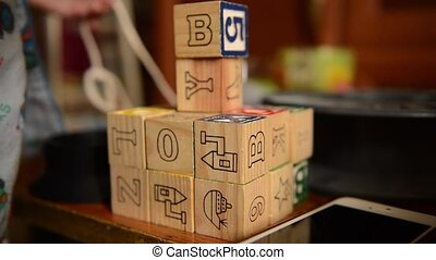 Baby playing with wooden developing dices.
