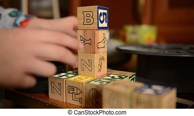 Baby playing with wooden developing dices. video filmed with...