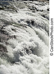 Rough and abundant river white flowing in vertical...