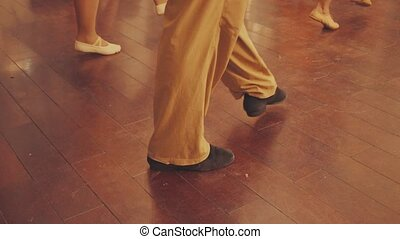 The legs of people dancing in the dance hall.