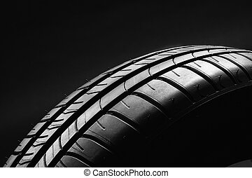 Summer fuel efficient car tire on black background - Studio...