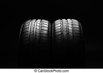 Summer fuel efficient car tires on black background - Studio...